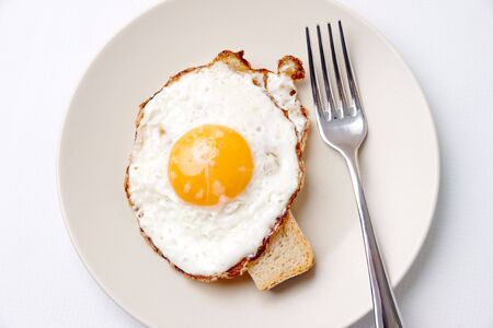 huevos fritos: Por encima de la vista de huevo frito en plato servido con pieza de pan de trigo