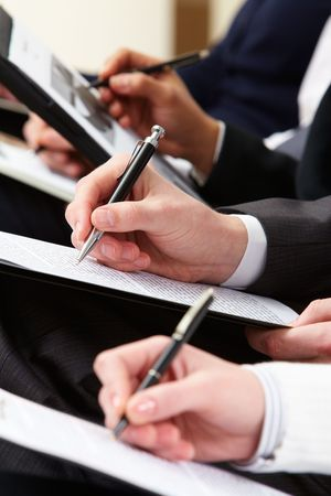 Close-up of business person hand with documents writing at lecture  photo