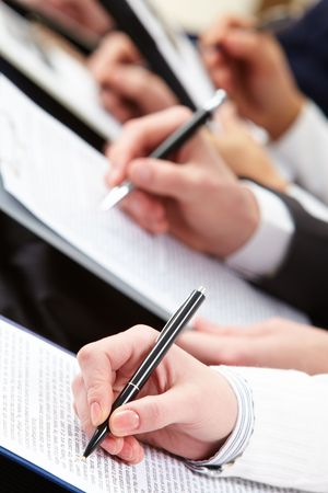 Close-up of business person hand making notes at lecture  photo