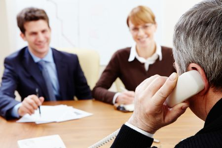 Rear view of aged businessman talking on the phone with his employees near by photo