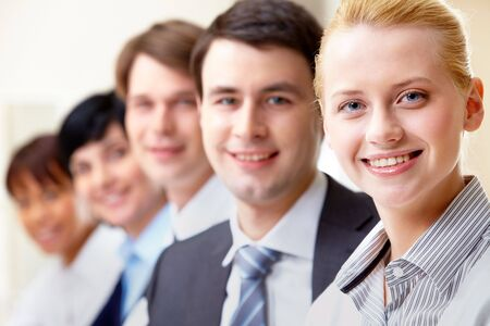 people in row: Confident businesswoman looking at camera with colleagues on background