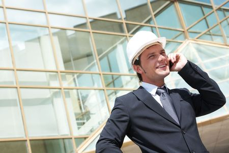 hardhat: Portrait of confident foreman in helmet calling by mobile phone Stock Photo