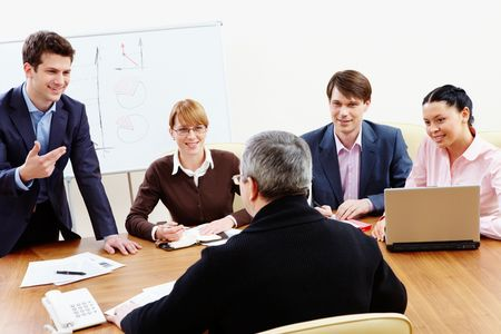 teacher training: Rear view of aged businessman making report to partners at conference Stock Photo