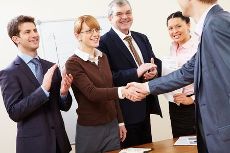 Photo of successful business partners handshaking after striking great deal with applauding people near by photo
