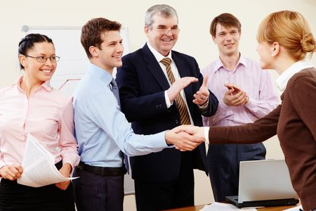 applauding: Photo of successful business partners handshaking after striking great deal with applauding people near by Stock Photo