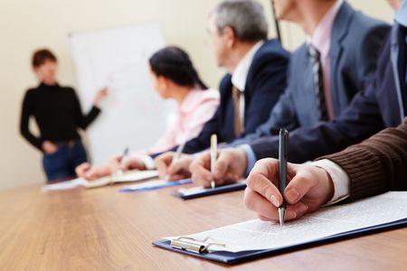 Fila de gente de negocios haciendo notas durante la presentación