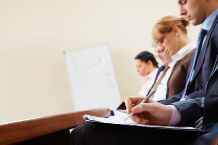 Close-up of businesspeople hands with documents writing at lecture  photo