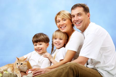 Portrait of joyful family looking at camera on blue background Stock Photo - 6700239