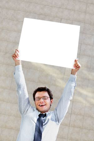 Image of successful male raising blank paper and looking at camera with smile Stock Photo - 6700204