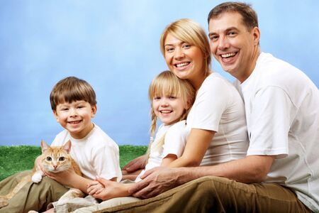 Portrait of joyful family and their cute pet looking at camera on blue background photo