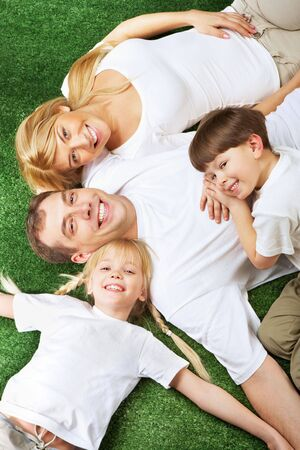 Above view of family members lying on green grass and smiling at camera Stock Photo - 6700252