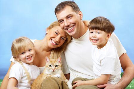 Retrato de miembros de la familia cariñosos mirando a la cámara sobre fondo azul