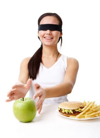 ojos vendados: Retrato de joven con sus ojos doblado decidir qué comer: una manzana o comida rápida