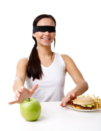 blindfold: Portrait of young girl in blindfold stretching her hand towards green apple and putting away fast food