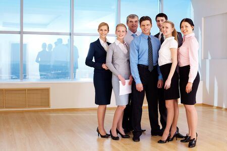 next to each other: Portrait of confident business group standing next to each other and looking at camera