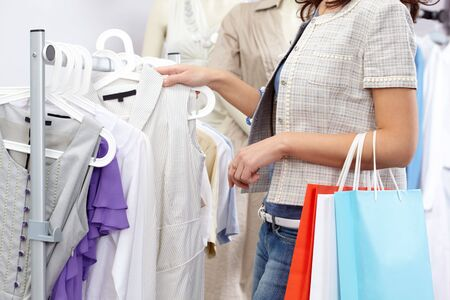 personal shopper: Close-up of female choosing new tanktop in clothing department