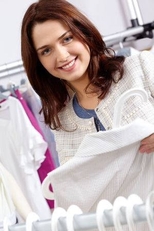 tanktop: Portrait of pretty woman choosing new tanktop and looking at camera in clothing department