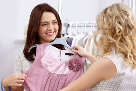 Image of pretty girl trying on tanktop with helpful assistant near by in the department store photo