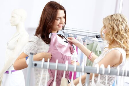 Image of pretty girl trying on tanktop with helpful assistant near by in the department store Stock Photo - 6715374