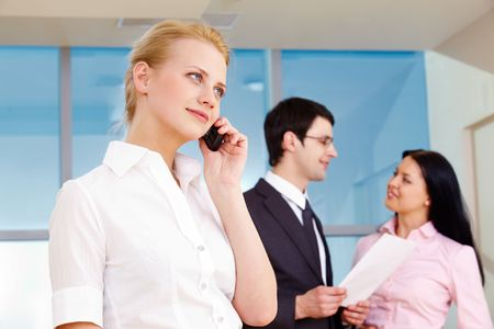 Image of pretty employee speaking on the phone in working environment Stock Photo - 6700446