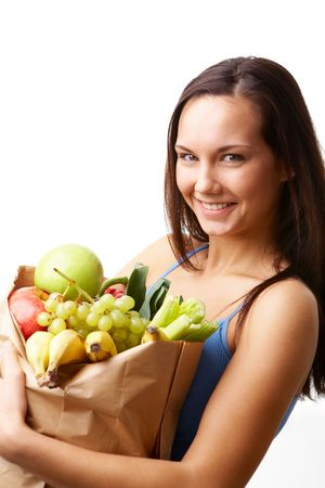 Portrait of pretty girl holding big paper sack in hands full of different fruits and vegetables photo