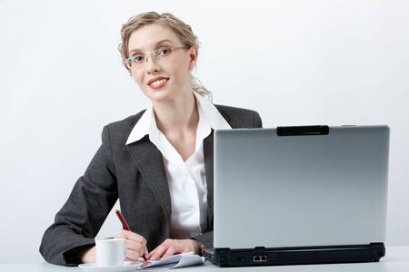 Image of young successful employer writing and looking at camera at workplace photo