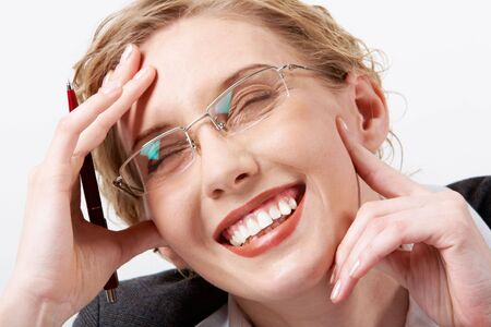 Image of happy woman in eyeglasses touching her face and laughing photo