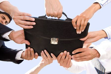 Below angle of people hands holding black leather briefcase simultaneously photo