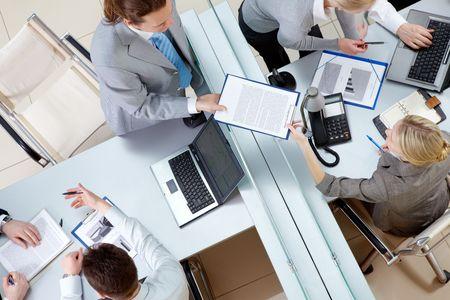 Por encima de ángulo de hombre confía en pasar el contrato a Secretario bonito en el entorno de trabajo