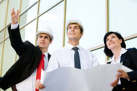 Confident worker pointing at something while explaining new project to his colleagues photo