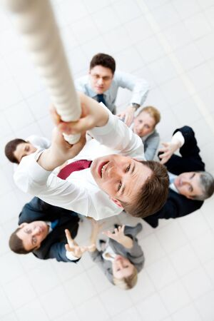 exertion: Above view of businessman ascending up the rope with his crew beneath
