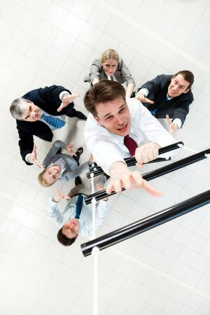 Above view of businessman ascending the ladder with his crew beneath photo