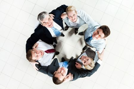 Above view of several business partners looking upwards at camera while embracing each other Stock Photo - 6714330