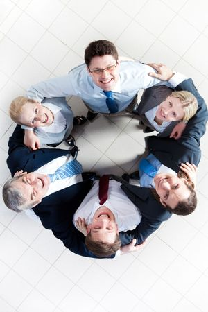Above view of several happy business partners looking at camera while embracing each other Stock Photo - 6714298