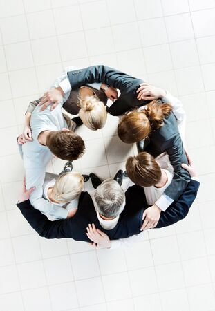 Above view of several business partners embracing each other and making circle Stock Photo - 6714195