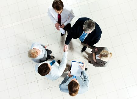 handshaking: Photo of successful business partners handshaking after striking deal with some employees near by Stock Photo