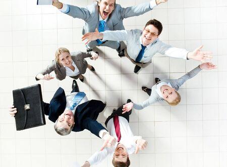 actitud positiva: Por encima de la vista de varios socios de �xito riendo y mirando la c�mara
