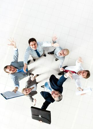 altogether: Above view of several successful partners laughing and looking at camera