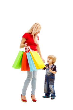 shoppings: Image of pretty female holding bags full of presents or shoppings with her son near by