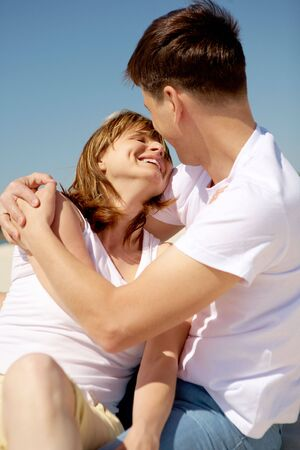 Portrait of amorous couple embracing against blue sky at summer photo