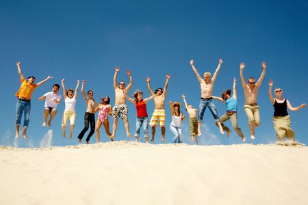Crowd of friends jumping on sandy beach with their arms raised against blue sky photo