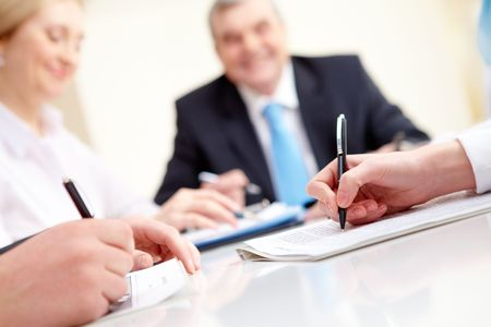Close-up of business partners hands over document with their boss on background Stock Photo - 6714174