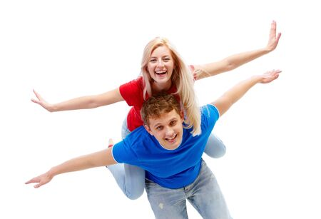 Photo of happy guy giving piggyback to joyful girl while both looking at camera Stock Photo - 6714203