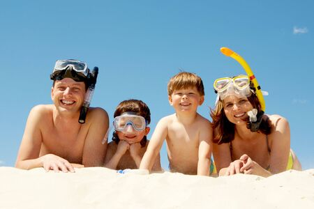 Portrait of diving family lying on sand against blue sky and smiling at camera Stock Photo - 6714145