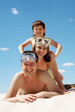 summertime: Portrait of cheerful couple in goggles and their son lying on sand