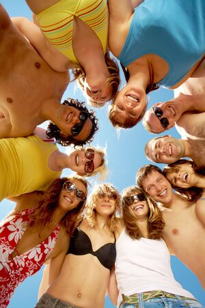 ниже: Below view of circle of friends looking at camera with blue sky above them