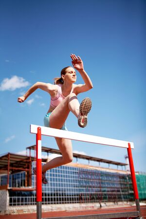 contestant: Image of young female jumping over barrier