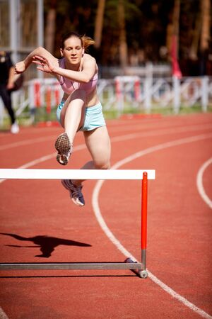 Image of young female running and getting ready to jump over barrier photo