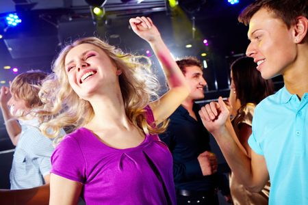 Photo of smiling friends dancing during the party