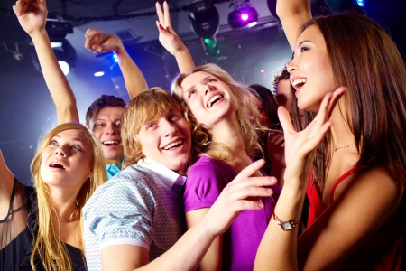 night club: Photo of smiling friends dancing during the party in excitement Stock Photo